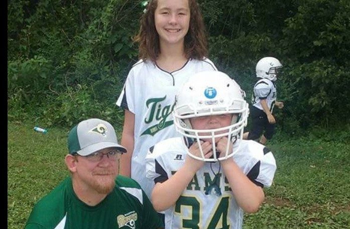 Roane Transportation employee and head of parts room, Jesse, with his two children, a son and daughter, at the son's football game.