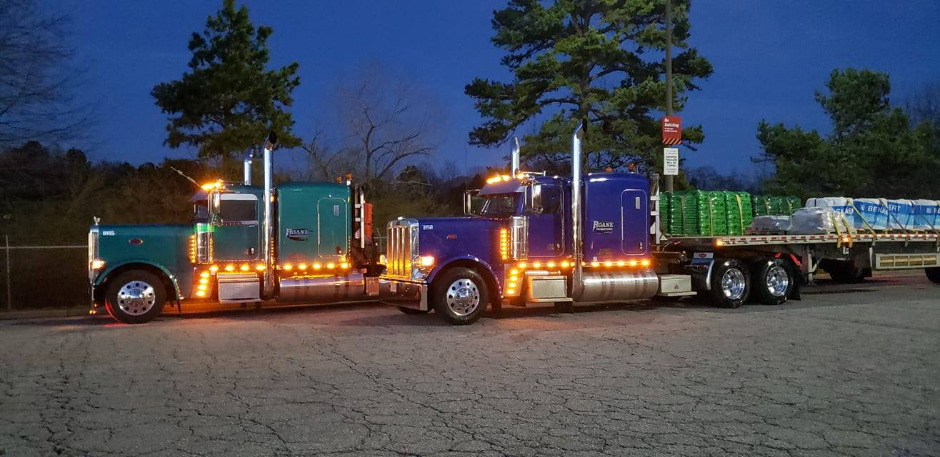 Two semi trucks hauling flatbeds sitting at a truck stop