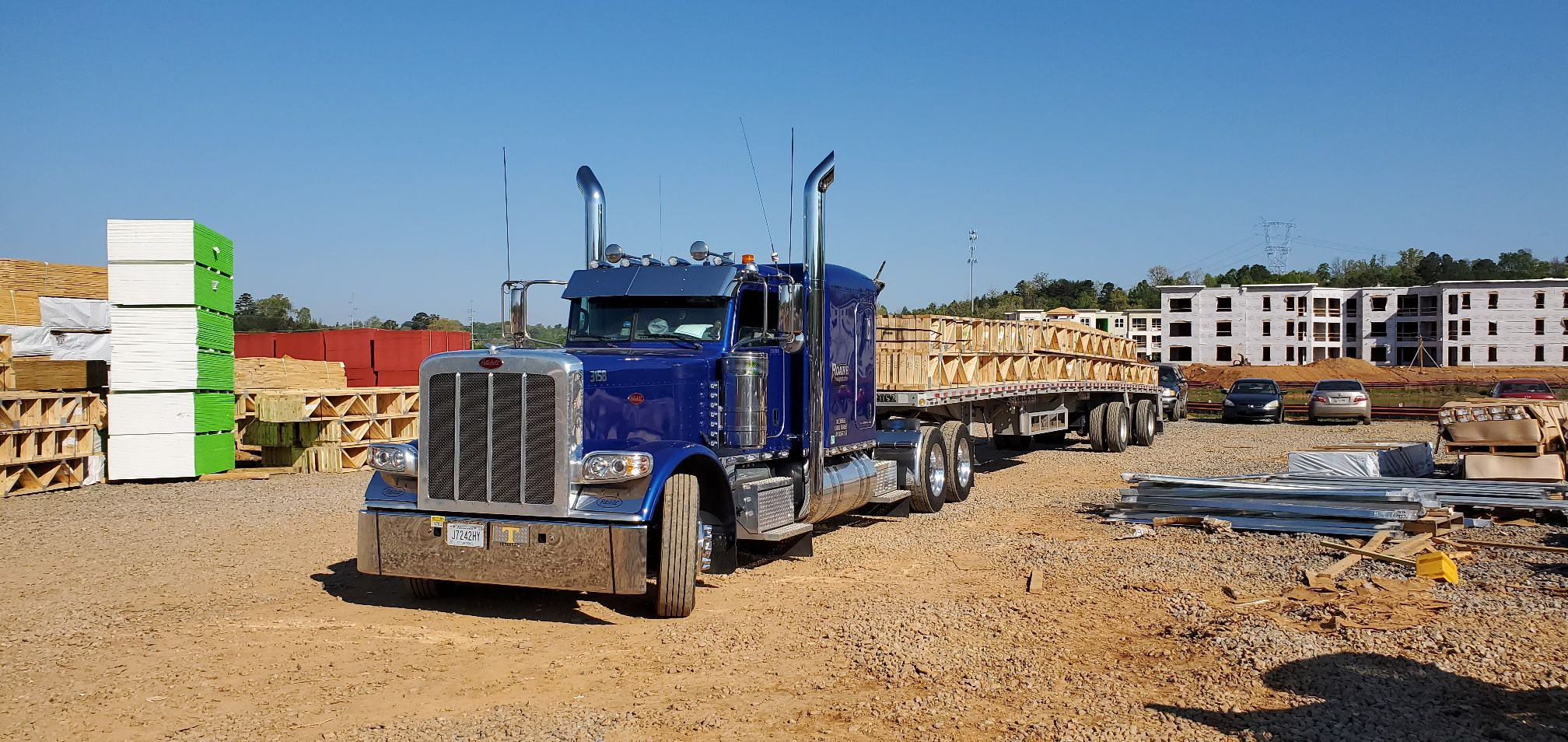 A roane transportation flatbed truck hauling something to a construction site