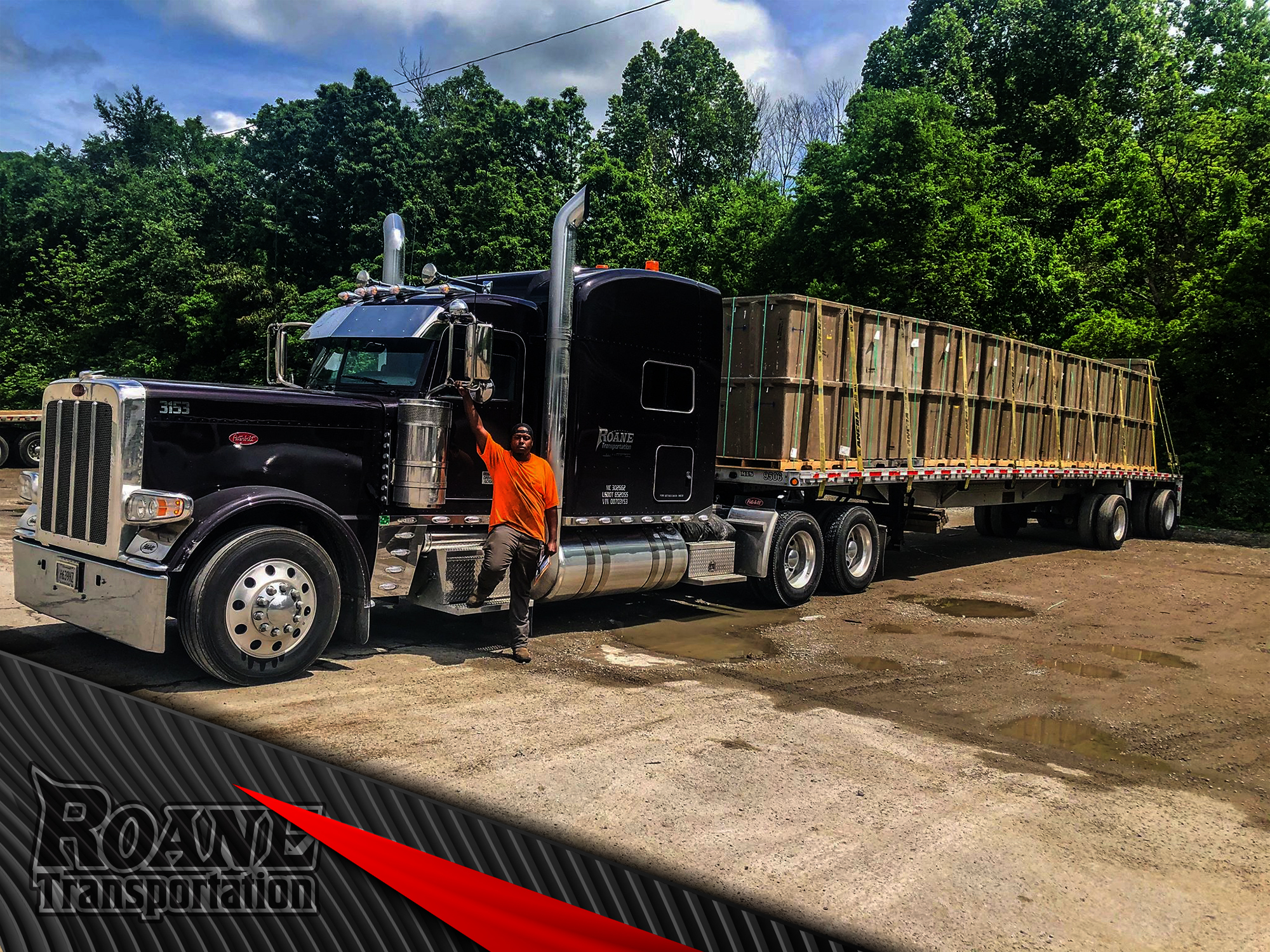 a proud truck driver standing in front of his new peterbilt given to him by roane transportation